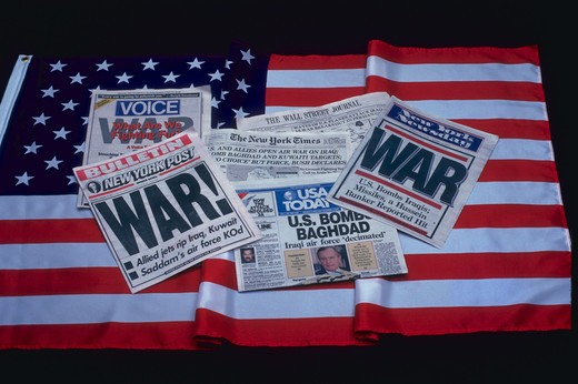 Stock Photo: 4286-32424 Still life of several newspapers with headlines announcing the Gulf War with Iraq laying on an American flag.