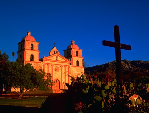 Stock Photo: 4286-32602 Sun shining on Mission Santa Barbara at sunrise, with cross in foreground.