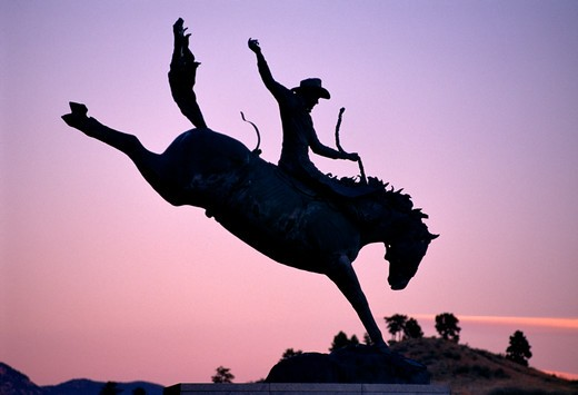 Stock Photo: 4286-32792 Silhouette of statue titled ?The Champ? of a horse and bronc rider at the Pro Rodeo Hall of Fame in Colorado Springs, Colorado.