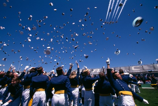 The United States Air Force (USAF) Thunderbirds fly over as USAF Academy Cadets toss their caps in the air at the completion of graduation ceremonies. : Stock Photo