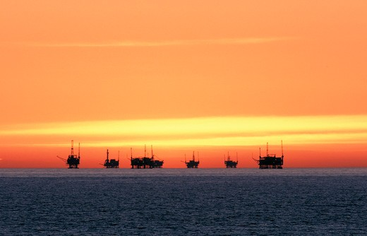 Orange sky over cluster of oil rigs outside Seacliff, California : Stock Photo