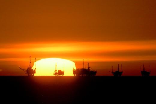 Sun sets behind oil rigs outside coast of California : Stock Photo