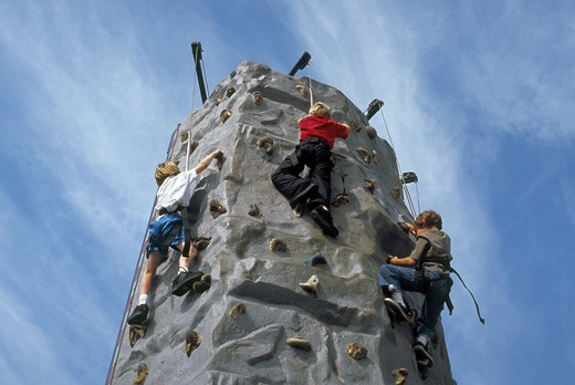 Children practicing mountain climbing on transportable wall : Stock Photo