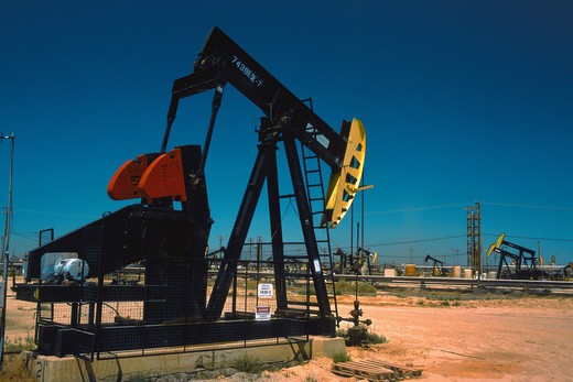 Oil extraction device pumping in a vast field in the San Joaquin Valley in California : Stock Photo
