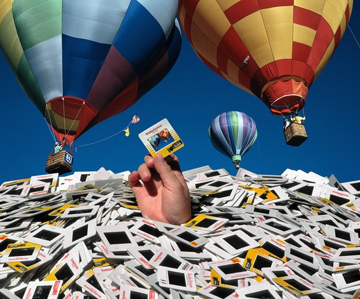 Hand holding slide sticking up from pile of transparencies against a backdrop of beautiful hot air balloons : Stock Photo