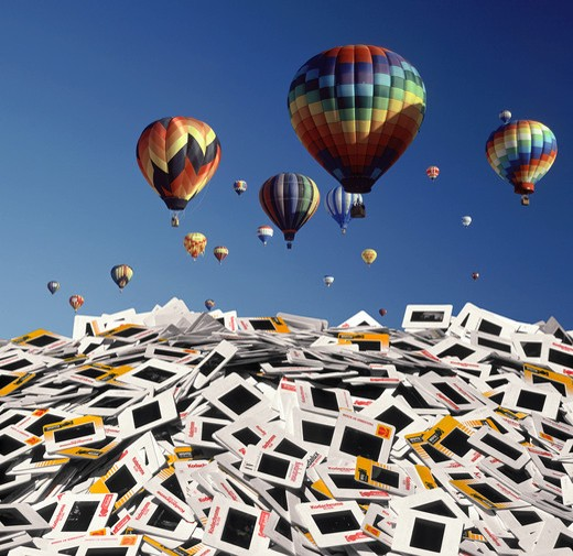 Large collection of beautiful hot air balloons hovering over pile of slides : Stock Photo