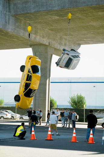 Two autos waiting to be dropped for action movie sequence under Interstate 105 near LAX, Los Angeles, California : Stock Photo