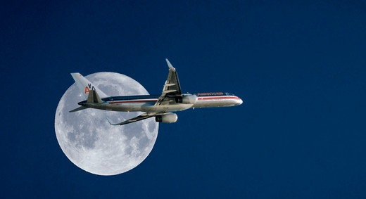 American Airlines Boeing 777 passing by the full moon : Stock Photo