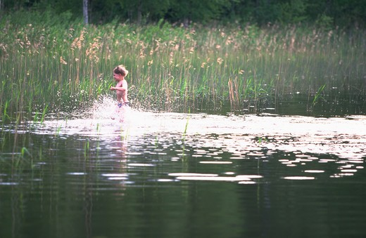 Stock Photo: 4286-35394 Young boy running through the water along a lake in Southern Finland.