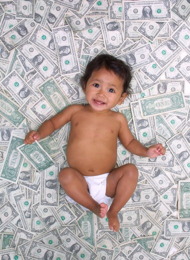 Stock Photo: 4286-35439 Southeast Asian Cambodian eleven month old baby girl lying in a pile of money.