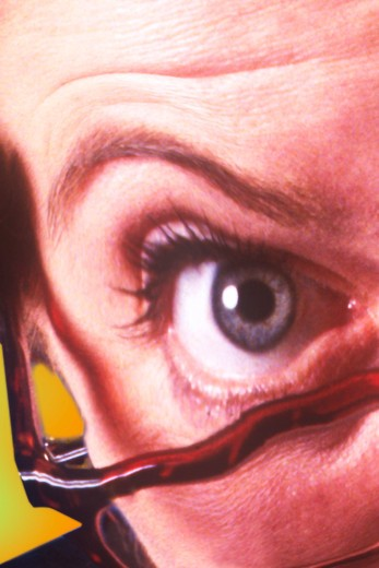 Distorted image of a woman?s eye and raised eyebrow looking out from behind glasses. : Stock Photo