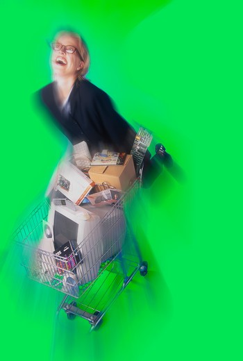 Stock Photo: 4286-35556 Blurred view of a woman pushing a shopping cart full of computer equipment and supplies.