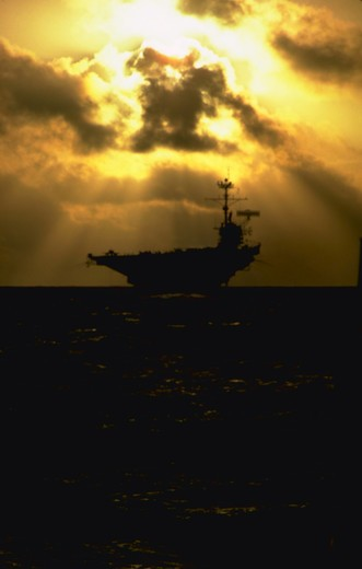 U.S. Navy aircraft carrier, operating in the Pacific Ocean.  Dramatic shot with interesting sky.  Taken from second ship, a U.S. Navy frigate following the carrier during a lull in flight operations, while in a ?plane guarding? role.(Water Series. Ocean.  Military. National Security.) : Stock Photo