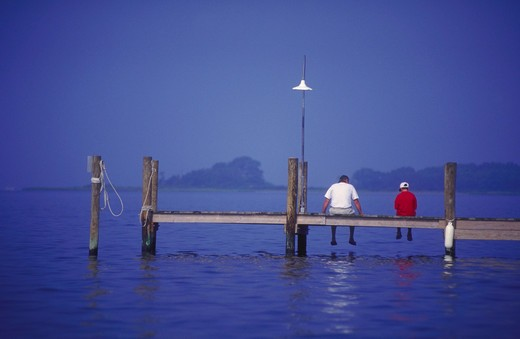Stock Photo: 4286-35725 Man and boy (father and son) sitting on a dock, on Rehoboth Bay, Delaware.