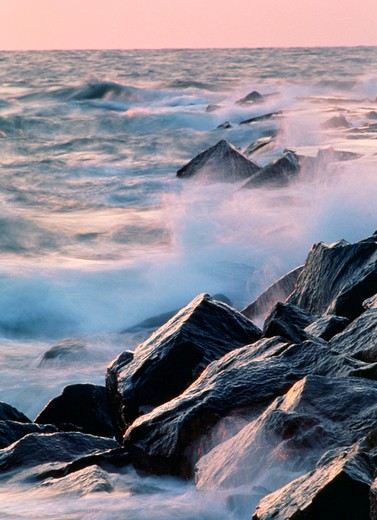 Ocean and waves, splashing on rocks, in early morning light.  Other variations available. (Landscape. Scenic. Water. Travel.) : Stock Photo