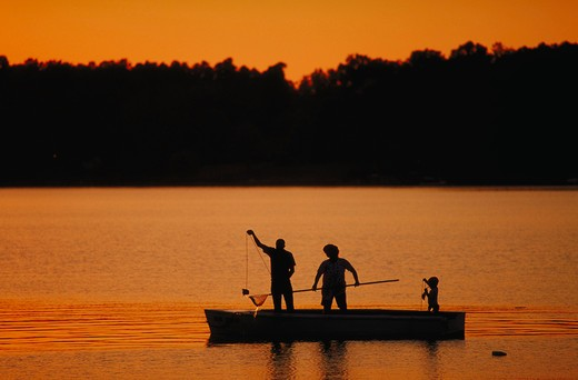 Silhouette of family fishing at sunset. : Stock Photo