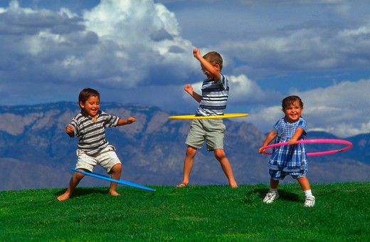 Stock Photo: 4286-36279 Three children playing with hula hoops on a grassy knoll.