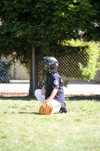 Stock Photo: 4286-36390 Young boy playing youth league baseball, catcher squatting