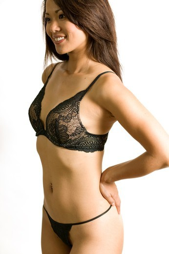 Portrait of a woman wearing netted bra and thongs. : Stock Photo