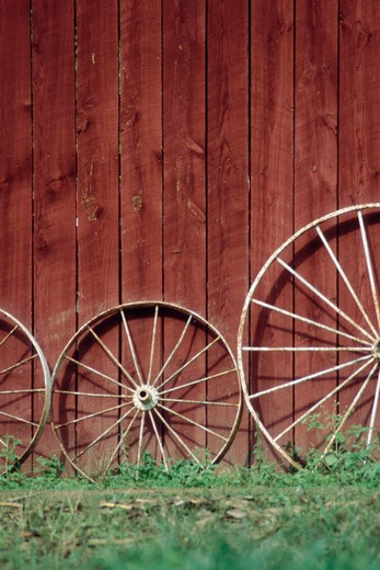 Wooden wagon wheels leaning against a red barn in western North Carolina. : Stock Photo