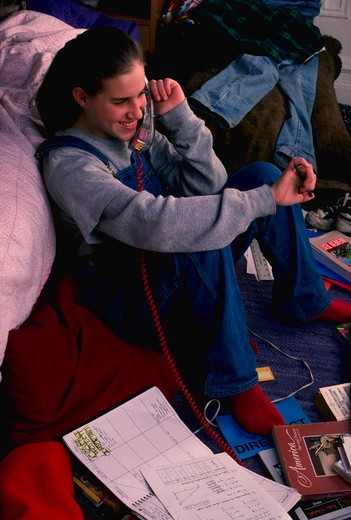 Stock Photo: 4286-39951 Teenage girl talking on phone in bedroom.