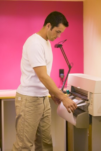 Stock Photo: 4286-40002 Man attending to printer plotter  MR-0406 PR-0407