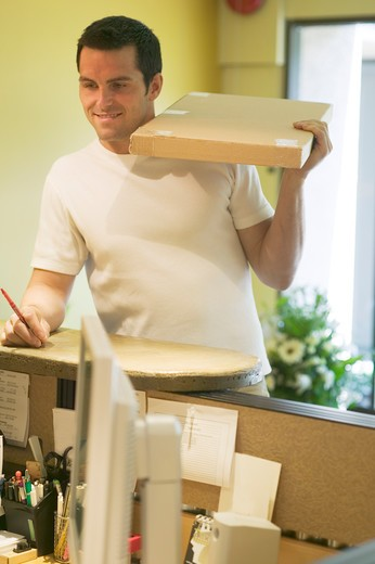 Stock Photo: 4286-40004 Courier delivering box to business reception  MR-0406 PR-0407