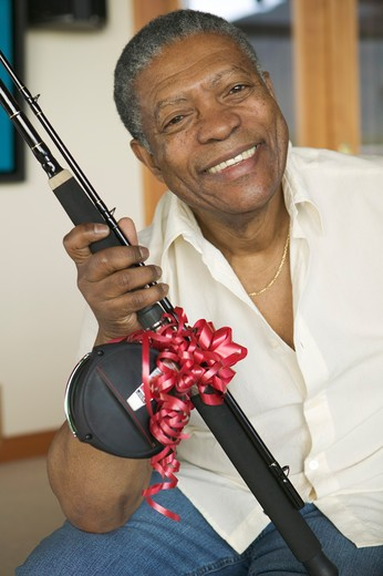 Stock Photo: 4286-40035 Senior, African American. Receiving fishing rod as gift.  MR-0509 PR-0505