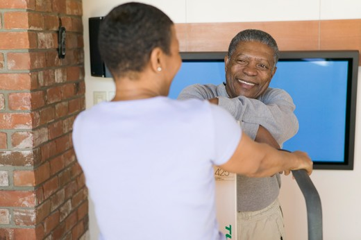 Seniors, African Americans. Exercising on stepper machine and plasma TV  MR-0509 MR-0510 PR-0505 : Stock Photo