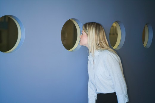 Stock Photo: 4286-40528 Business woman looking through port holes.  MR-0538 PR-0527