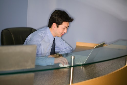 Stock Photo: 4286-40545 Asian male at reception desk.  MR-0525 PR-0527