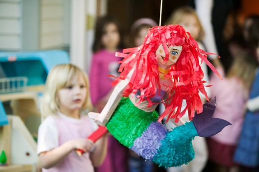 Children Trying to Break Open a Pinata at a Birthday Party : Stock Photo