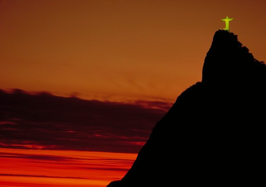 The statue of Christ the Redeemer (Corcovado) standing high atop a hill at sunset against an orange sky in Rio de Janeiro, Brazil. : Stock Photo