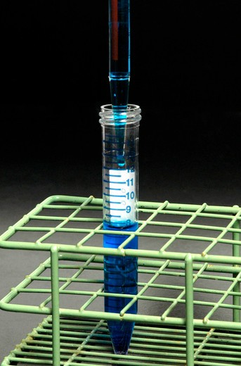Stock Photo: 4286-43069 A pipette is used to pour a blue liquid into a test tube which stands alone in a wireframe holder.