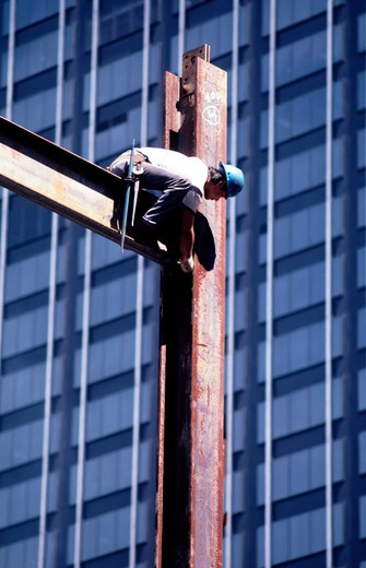 Construction worker on a steel beam connecting girders together.  : Stock Photo