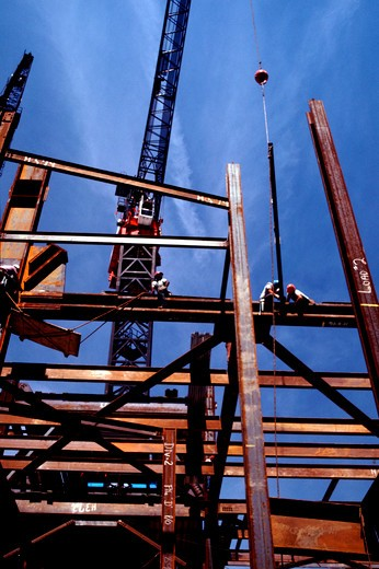 Stock Photo: 4286-43114 Construction workers high above ground on steel beams with a large crane behind the skeletal structure of the future building.