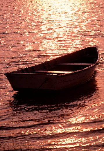Stock Photo: 4286-43162 Late afternoon sun lights up a row boat floating in the water, East Marion, NY.