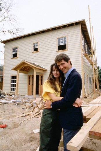 Couple in front of home under construction : Stock Photo