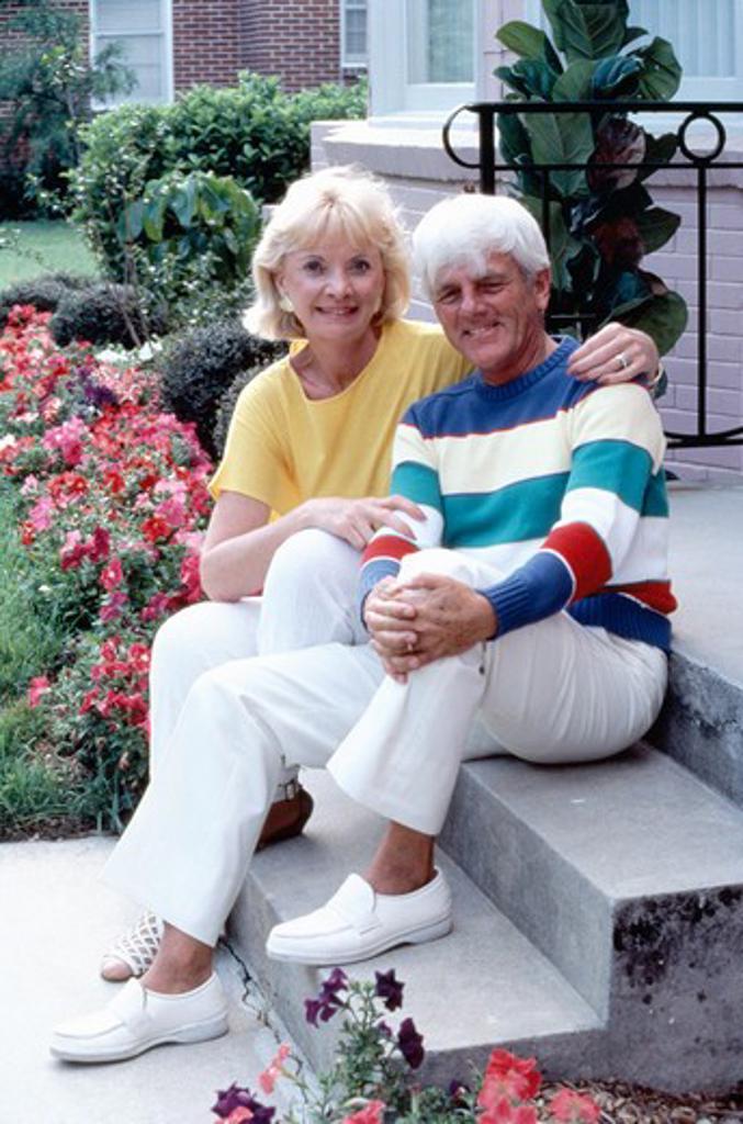 Senior couple sitting on front steps : Stock Photo