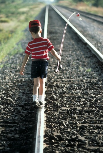 Boy walking on train tracks, with fishing pole, MR : Stock Photo