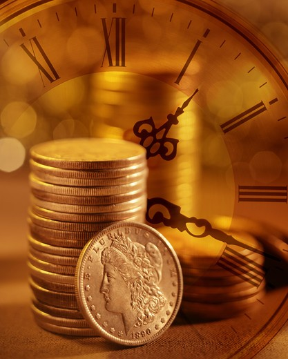 Stock Photo: 4286-43745 Montage of a stack of silver dollar coins with a clock.