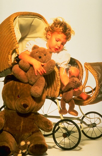 Stock Photo: 4286-43804 Young girl playing in antique stoller with teddy bears.