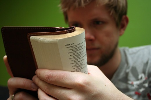 Young blond man reading the Bible with bright green background : Stock Photo