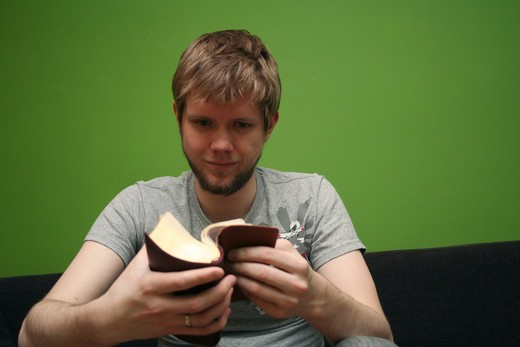 Stock Photo: 4286-44019 Young blond man reading the Bible with bright green background