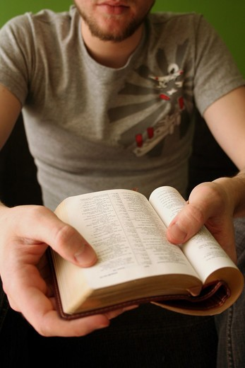 Stock Photo: 4286-44026 Young blond man reading the Bible with bright green background