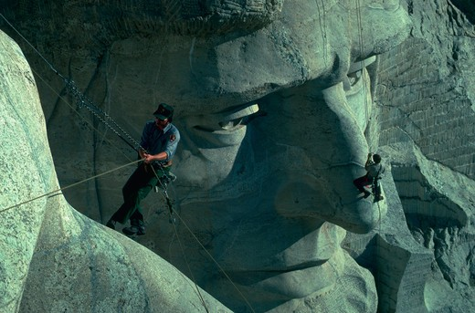 Two workers examine cracks in the faces at Mt. Rushmore. : Stock Photo