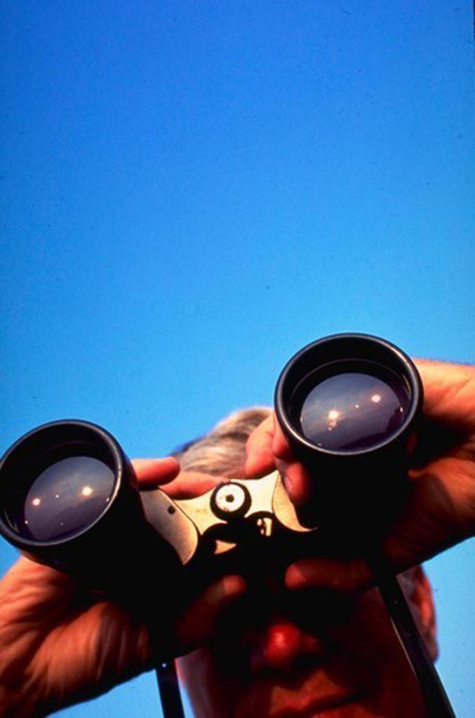 Man looking through binoculars. : Stock Photo