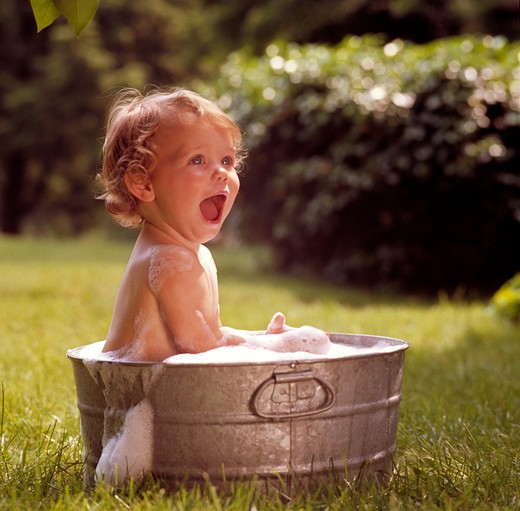 Stock Photo: 4286-52820 Toddler sitting in an aluminum tub outside taking a bath as the soap suds overflow.