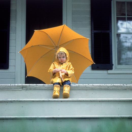 Portrait of a young child wearing a yellow rain coat and rain boots holding an umbrella sitting on the front porch of a house. : Stock Photo
