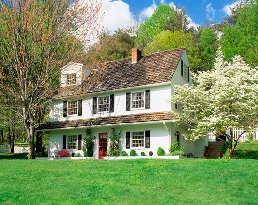 Stock Photo: 4286-53144 Exterior view of front of three story white frame house with cedar shake shingles and flowering dogwood tree. Property released.